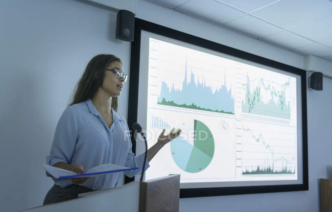Businesswoman making presentation using screen of charts and graphs — Stock Photo