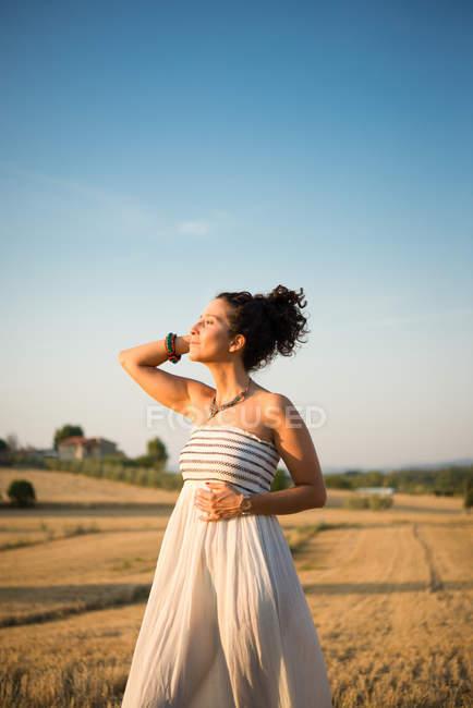 Взрослая женщина, стоящая в поле и наслаждающаяся солнцем — стоковое фото