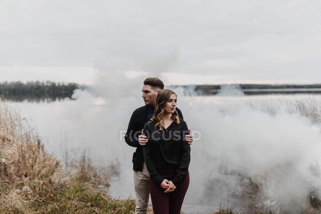 Casal jovem pela nuvem de fumaça olhando para longe, Ottawa, Canadá — Fotografia de Stock