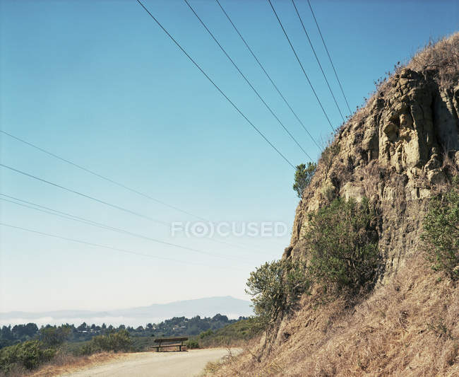 Lonely bench near road and cliff — Stock Photo