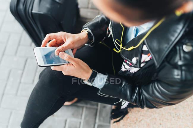Женщина сидит со смартфоном и чемоданом рядом — стоковое фото
