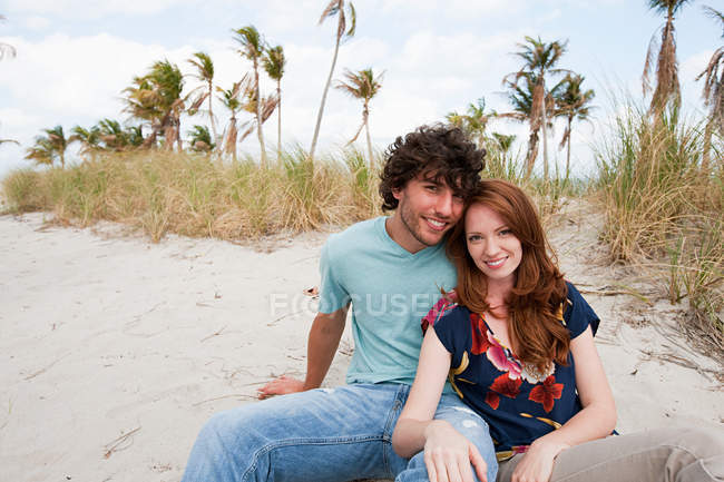 Portrait of young couple sitting on beach — Stock Photo