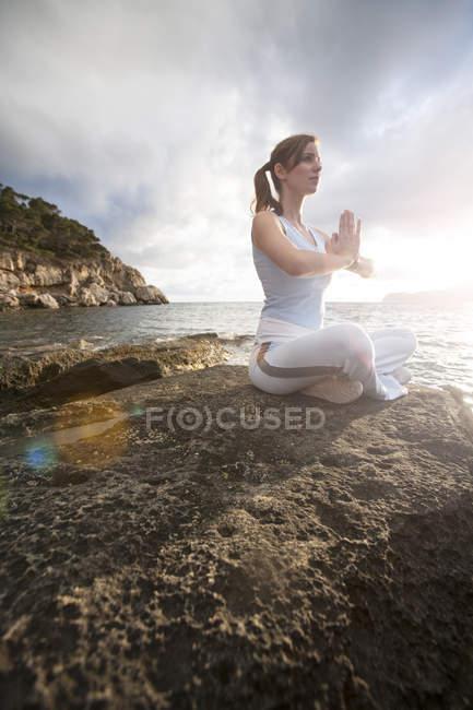 Woman sitting on rocks by sea and meditating, Palma de Mallorca, Islas Baleares, Spain, Europe — Stock Photo