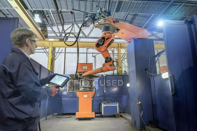 Инженер с контроллером роботизированной сварки Бей в машиностроительный завод — стоковое фото