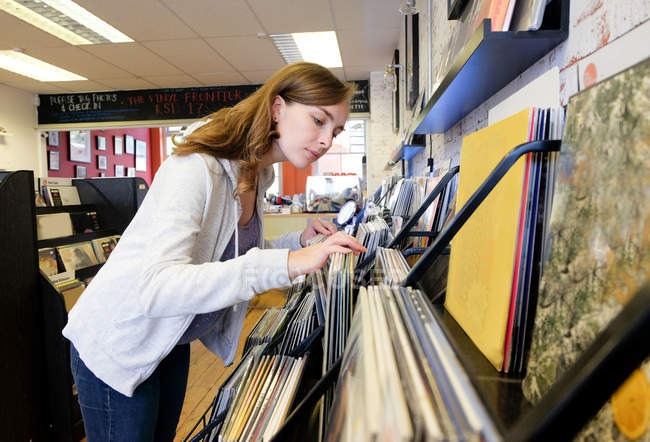 Jeune femme regardant vinyles empilés dans le magasin de disques — Photo de stock