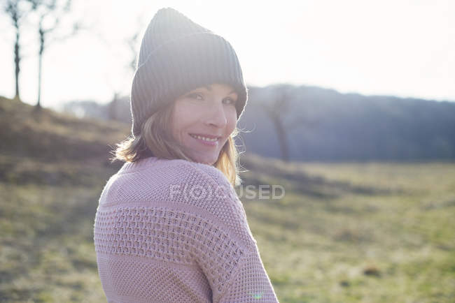 Portrait of woman in sunlit field looking over shoulder — Stock Photo