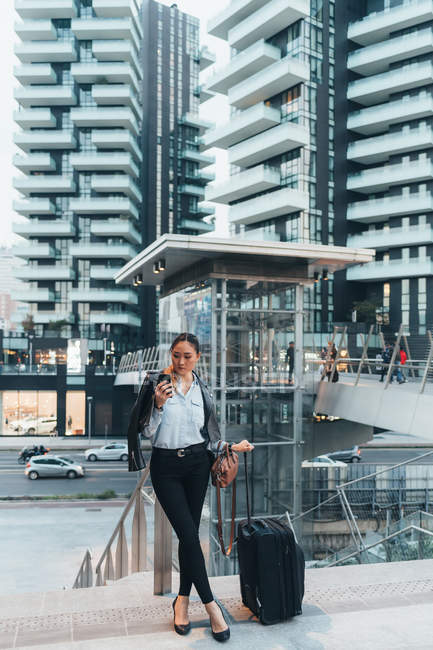 Businesswoman with wheeled suitcase using smartphone outdoors — Stock Photo