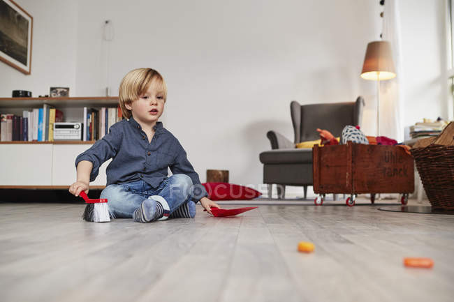 Молодий хлопчик, сидячи на підлозі з іграшку совок і пензликом — стокове фото