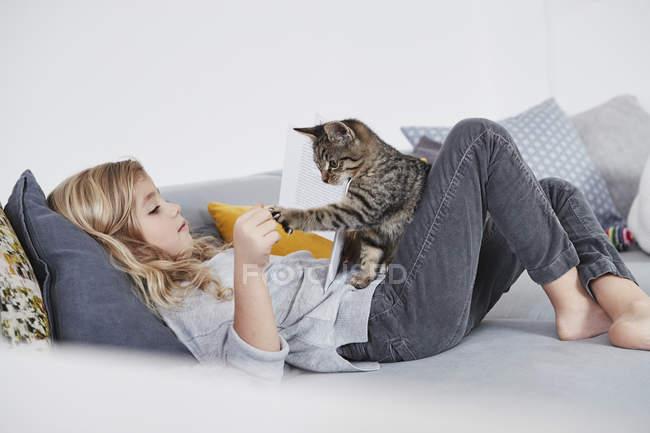 Молода дівчина на дивані, граючи з кота улюбленця — стокове фото