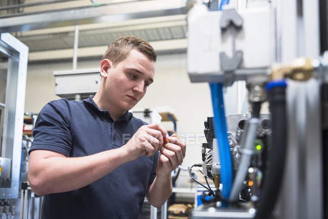 Male factory worker repairing equipment — Stock Photo