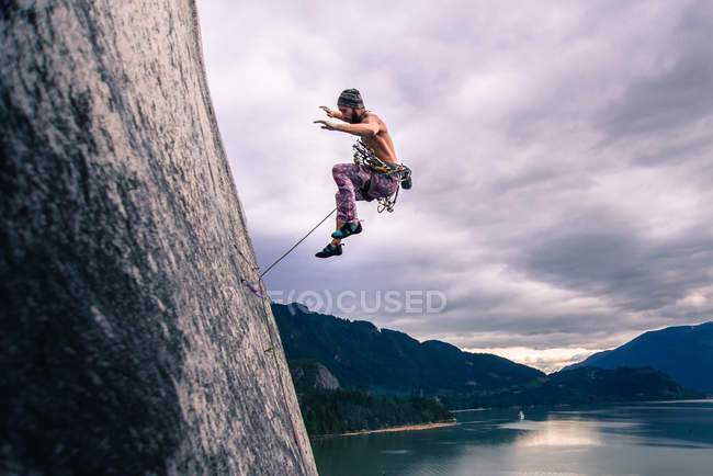 Side view of Man with climbing rope jumping off rock face on Malamute, Squamish, Canada — Stock Photo