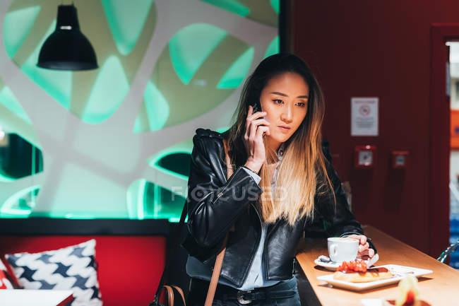 Жінка в бар пити каву і за допомогою смартфона — стокове фото