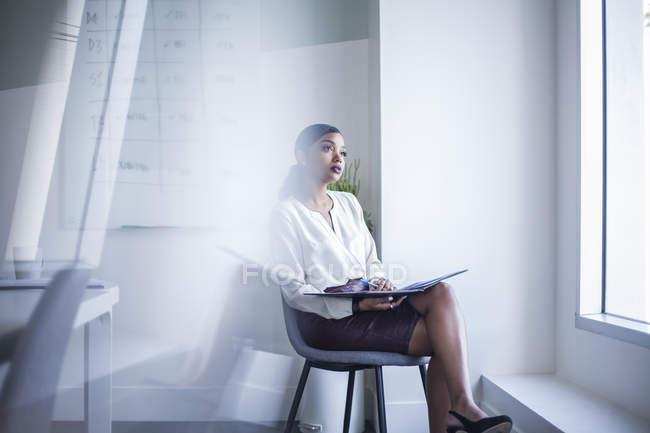 Donna di affari che si siede in ufficio e guardando fuori della finestra — Foto stock