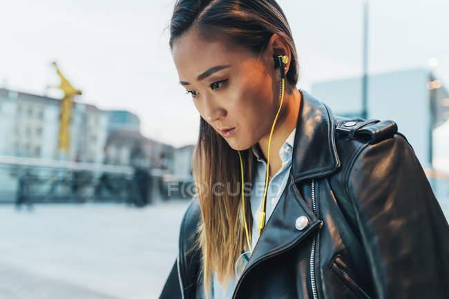 Donna in auricolari guardando oggetto fuori tiro — Foto stock