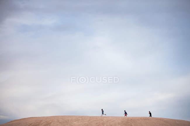 Vista a distanza di tre ragazzi che camminano sulla collina — Foto stock