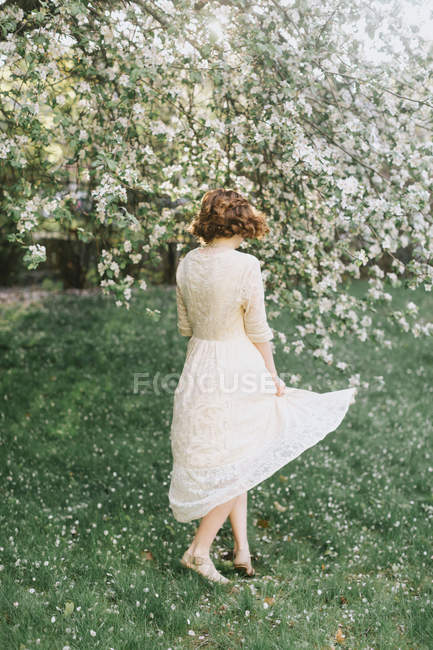 Woman in white dress twirling by blossom tree — Stock Photo