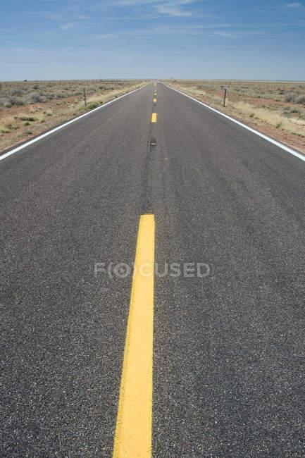 Empty road with yellow lines in desert, Arizona, United States of America — Stock Photo
