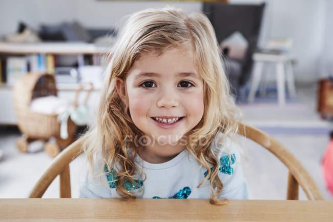 Портрет молодої дівчини, сидячи за столом — стокове фото