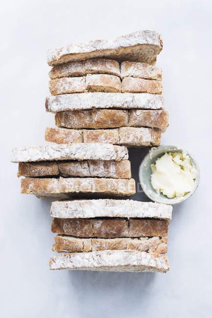 Draufsicht der Scheiben Brot mit Butter auf weiße Tischplatte — Stockfoto