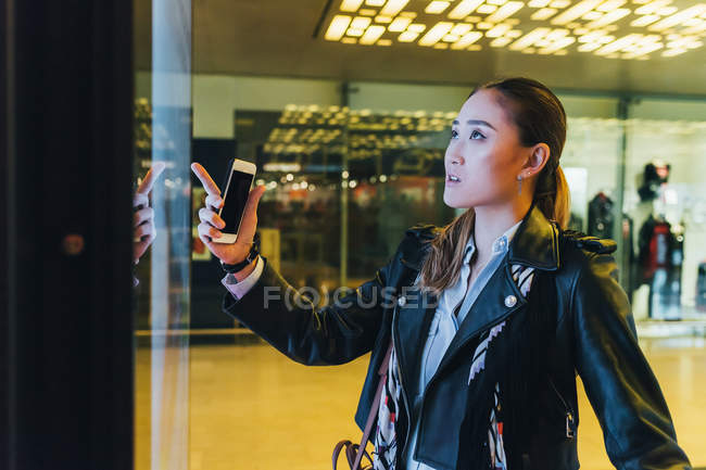 Woman holding smartphone and looking in store window — Stock Photo