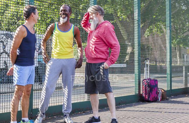 Трое взрослых мужчин разговаривают на баскетбольной площадке — стоковое фото