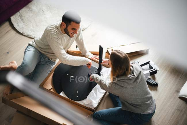 Couple assemblant les meubles de paquet plat — Photo de stock