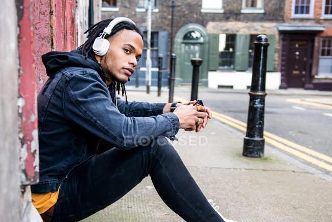 Mann mit Kopfhörer sitzt auf der Straße — Stockfoto