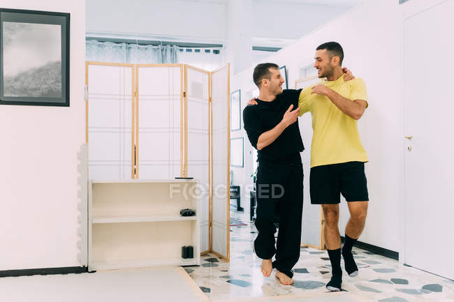 Friends in gym with arms around each other — Stock Photo