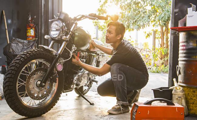 Mechanic working at custom motorbike shop, Bangkok, Thailand — Stock Photo