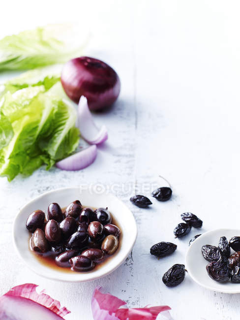 Cos lettuce, olives and red onions on white tabletop — Stock Photo
