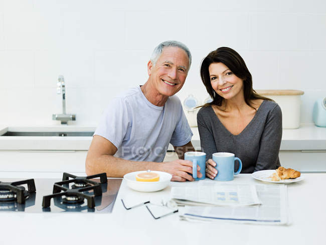 Mature couple at breakfast smiling at camera — Stock Photo