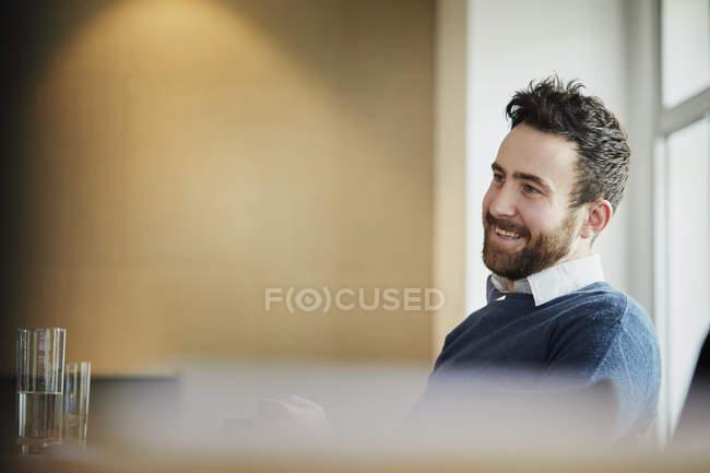 Бізнесмен в офісі фотографіях хтось дивитися вбік і посміхається — стокове фото
