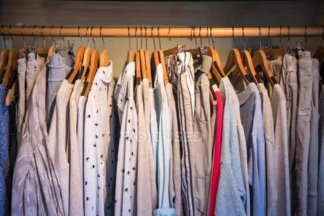 Blouses, shirts and pants on rail in shop — Stock Photo