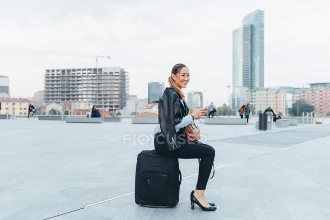 Ritratto di donna d'affari seduta sulla valigia all'aperto — Foto stock