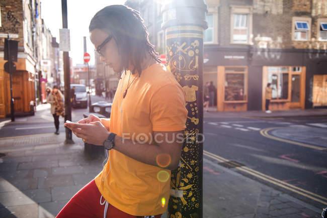 Молодой человек опирается на фонарный столб с помощью смартфона — стоковое фото