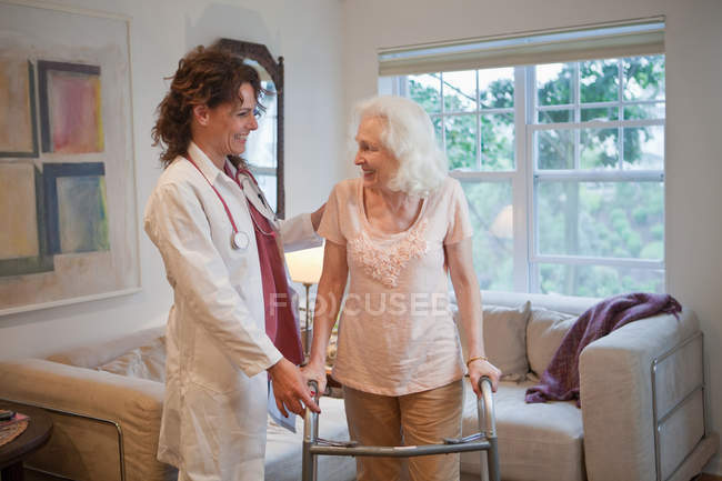 Doctor supporting senior woman on walking frame — Stock Photo