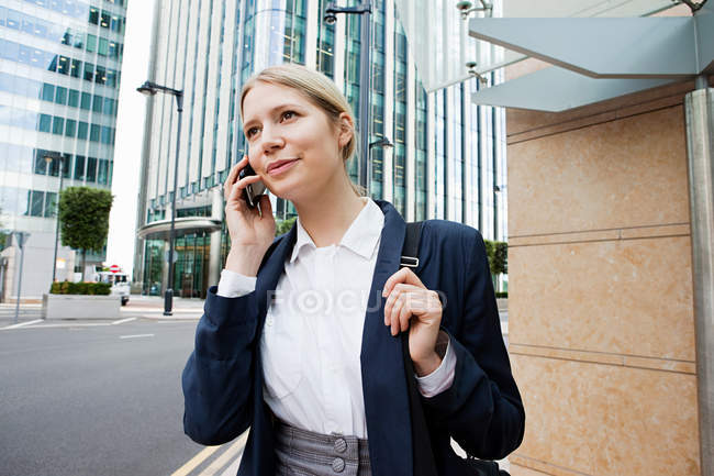 Young businesswoman talking on phone in city — Stock Photo