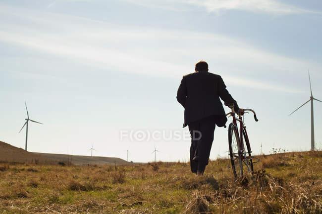 Visão traseira do homem puxando a bicicleta para cima contra o parque eólico — Fotografia de Stock