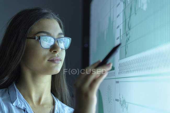 Businesswoman studying graphs on interactive screen in business meeting — Stock Photo