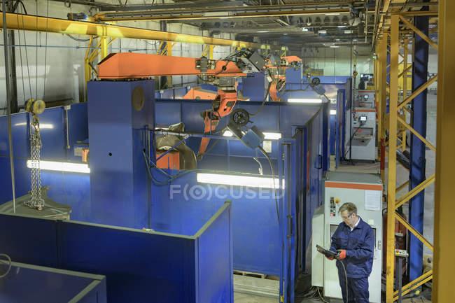 Высокий угол обзора робота-сварщика и рабочего на машиностроительном заводе — стоковое фото