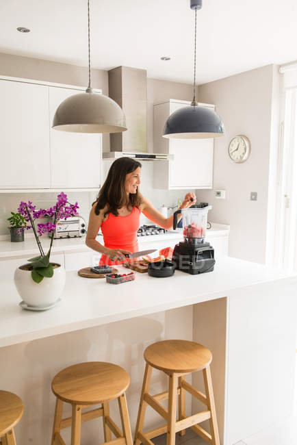 Femme préparant smoothie de melon d'eau dans un mélangeur — Photo de stock