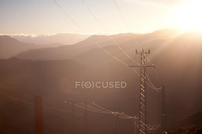 Montanhas e cabos telefônicos à luz do sol — Fotografia de Stock