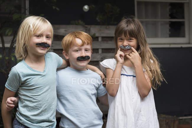 Crianças com bigodes falsos, olhando para a câmera — Fotografia de Stock
