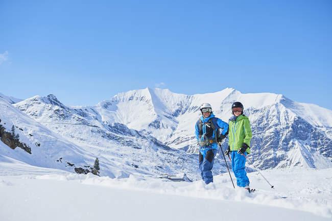 Отец и сын на лыжах с горы на фоне, Хинтертукс, Тироль, Австрия — стоковое фото