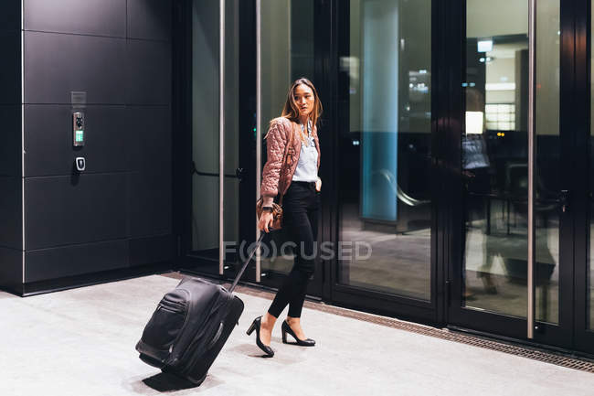 Woman by building pulling wheeled suitcase — Stock Photo