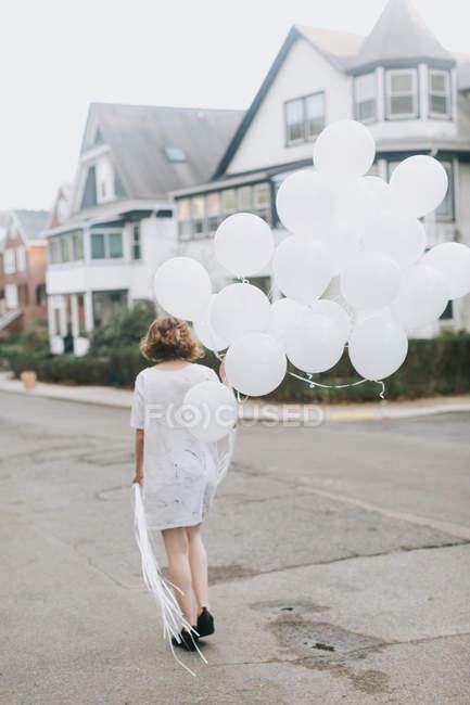 Femme dans la rue tenant un tas de ballons, Boston, Massachusetts, États-Unis — Photo de stock