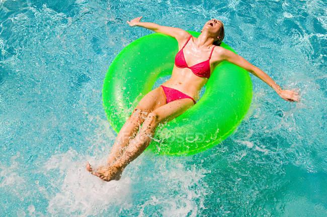 Jovem mulher flutuando no anel inflável verde na piscina — Fotografia de Stock