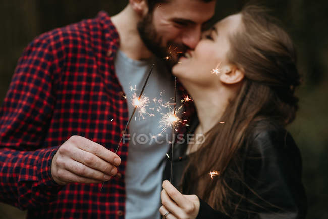 Close up of couple holding sparklers and kissing — Stock Photo