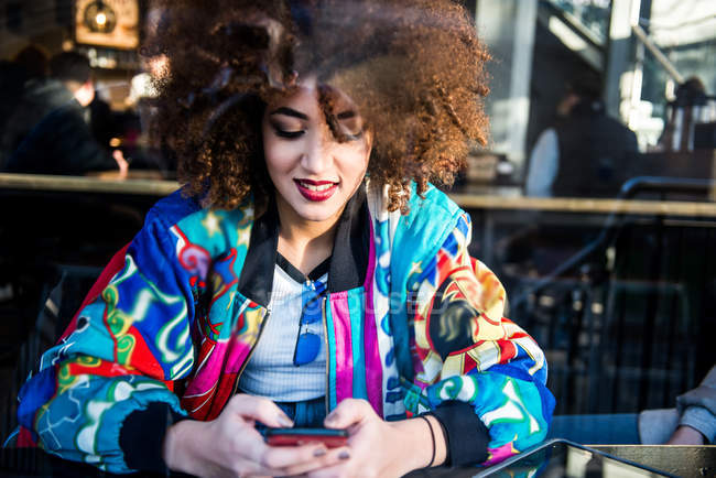 Young smiling girl sitting in bar, using smartphone, view through window, London, England, UK — Stock Photo