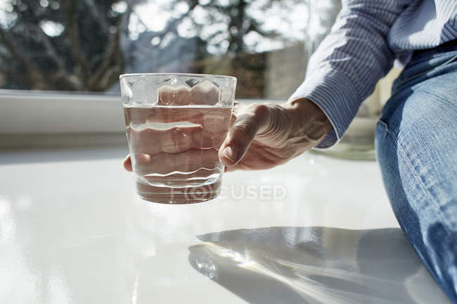 Senior woman holding glass of water, close-up partial view — Stock Photo